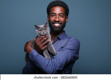 Beautiful afro man with a cat in front of a background