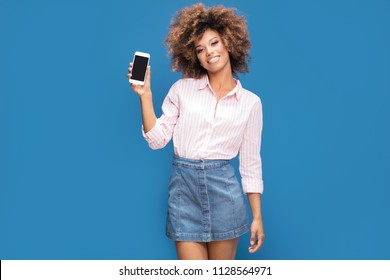 Beautiful afro woman showing mobile phone and smiling, standing on blue background. Girl wearing jeans short skirt and elegant shirt in white and pink stripes.