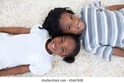 Beautiful Afro-American brother and sister on floor with heads together