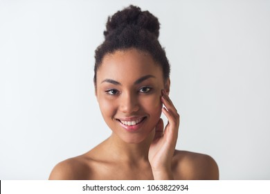 Beautiful Afro-American girl is touching her face, looking at camera and smiling, isolated on white