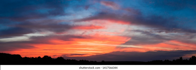 Beautiful afterglow blue sky with orange clouds fired by hidden sun. Countryside dark silhouette on foreground. Lower clouds drop diagonal shadow on upper clouds.