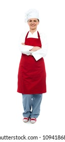Beautiful aged female chef posing in uniform with arms crossed, full length portrait