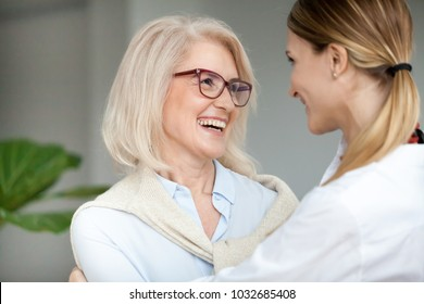 Beautiful aged woman in glasses embracing young adult lady and laughing, smiling attractive senior older mother happy to hug grown-up daughter, warm sincere family bonding having fun together