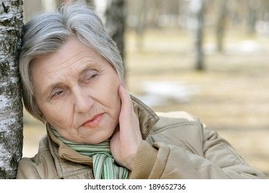 Beautiful aged woman on a walk outdoors in spring