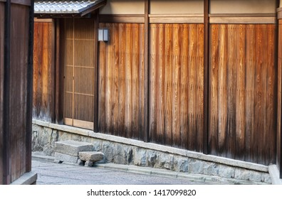 Beautiful aged wooden wall of traditional Japanese building on stone alleyway