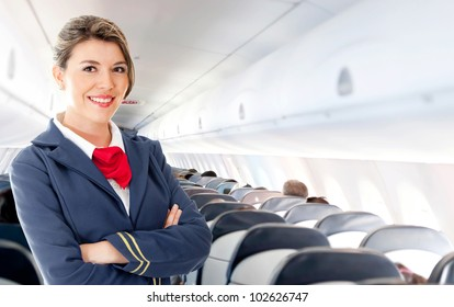 Beautiful air hostess in an airplane smiling