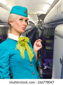 Beautiful air hostess in an airplane smiling
