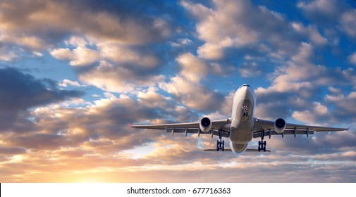 Beautiful airplane. Landscape with white passenger airplane is flying in the blue sky with clouds at colorful sunset. Travel background. Passenger airliner. Business trip. Commercial aircraft