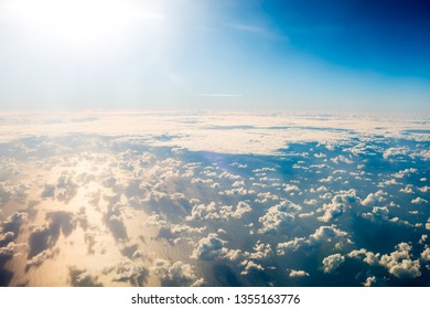 Beautiful airview with blue sky, white fluffy clouds and bright sunrays above them. Can be used as natural background