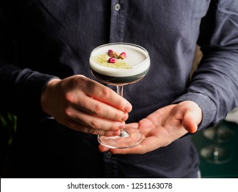 Beautiful Alcoholic Cocktail with egg white foam and dried flowers in male hands