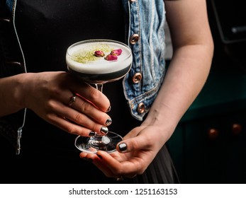 Beautiful Alcoholic Cocktail with egg white foam and dried flowers in female hands