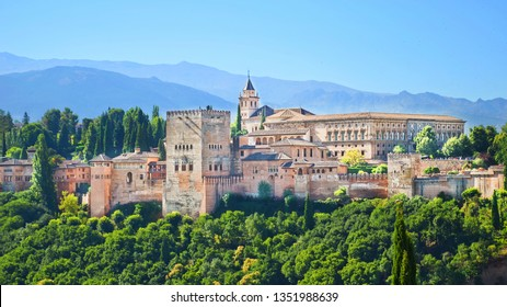 Beautiful Alhambra Palace complex in Spanish Granada on a sunny day captured on 16:9 photography. The amazing fortress and popular tourist spot is surrounded by green woods and mountains.