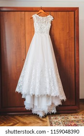 Beautiful A-line wedding dress with floral embroidery is hanging in the morning of a wedding day