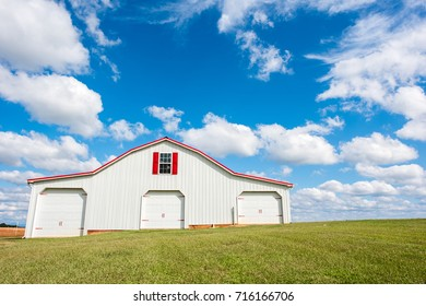 Beautiful all american red and white barn in a grassy field in southern america with a bright, blue sky and fluffy clouds behind.