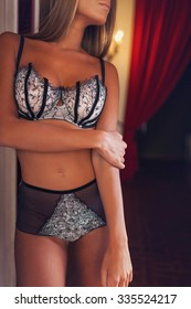 Beautiful alluring young woman in sexy lingerie in a bedroom. Studio shot