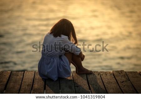 Beautiful alone girl on the beach, when sunset