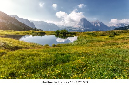 Beautiful alpine countryside with fairy lake. Awesome Alpine highlands in sunny day. Amazing Nature Scenery of Dolomites Alps. Great Scene in the mountains, place near Seceda peak. Val Gardena. Italy