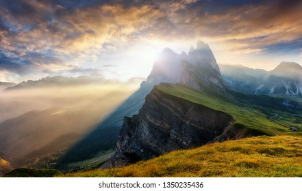 Beautiful alpine highlands with dramatic sky. Incredible view in Dolomite Alps. Awesome nature Landscape. View from Seceda peak on Famous Odle peaks under sunlight during sunrise. Bolzano, Italy,