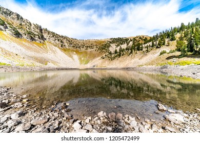Beautiful alpine lake with calm water and reflection of the mountain peak in Wyoming Bridger Teton National Forest near Jackson WY