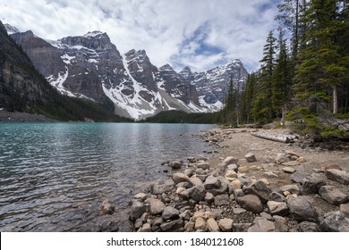 Beautiful alpine lake with turquoise waters surrounded by magnificent peaks, wide shot made on a overcast day at Moraine Lake, Banff National Park, Alberta, Canada