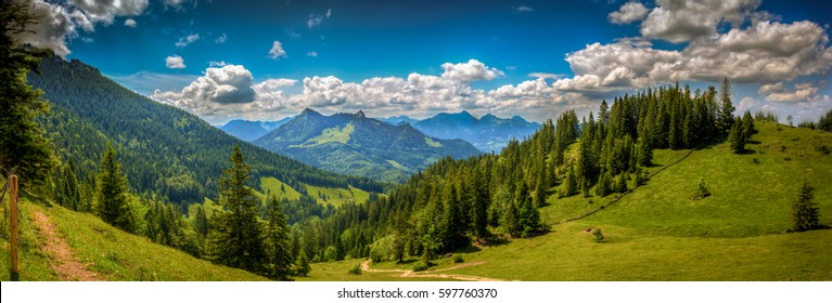 Beautiful alpine landscape with green hills and conifer forest, clouds in blue sky. Picturesque panoramic view of nature