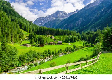 Beautiful alpine landscape with green meadows, alpine cottages and mountain peaks, Zillertal Alps, Austria