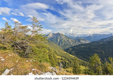 Beautiful alpine landscape with rocky mountains, grass and forests in the Ammergau Alps (Bavaria, Germany). Blue sky with clouds. Zugspitze, highest mountain of Germany, in the background.