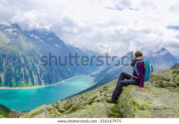 Beautiful alpine landscape with young woman and azure mountain lake in the background, Zillertal Alps, Austria
