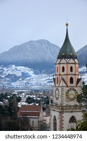 The beautiful Alpine town of Meran / Merano in south Tyrol, covered in snow in the winter.  Cathedral bell tower in the foreground.