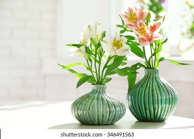 Beautiful Alstroemeria flowers in aquamarine vases on window background