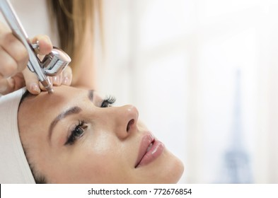 Beautiful and amazing attractive woman doing face treatment in beauty spa salon. Oxygen dermapen therapy. Space for text on white wall.
