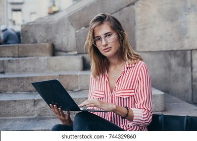 Beautiful and amazing blonde model in red shirt, with long straight hair, in trendy fashionable prescription glasses sits on stairs of office building or museum, works or study on laptop outdoors