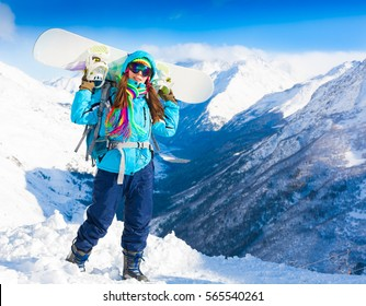 Beautiful amazing day winter mountains. A woman holding snowboard. Sport hike in holidays. Landscape inspiring. Cool fun girl. Blue sky and white snow. Happy hobby.