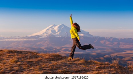 Beautiful amazing landscape.  Mountains in country Russia Caucasus. Unique Bermamyt plateau.  Woman enjoy hiking on Elbrus background. Active sport hobby. Autumn panorama.