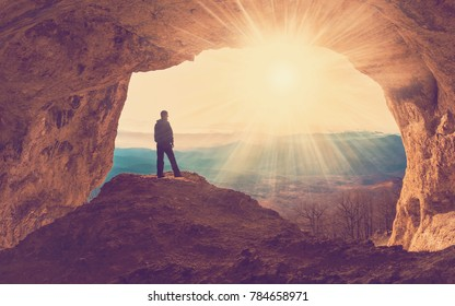 Beautiful amazing sunset.  Mountains in north country Russia Caucasus. Unique landscape mainsail.  Silhouette of a man. Old cave. Active sport and hobby. Spelunking background.