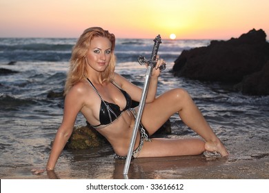 Beautiful amazon soldier girl with sword sitting on a seaside