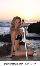 Beautiful amazon soldier girl with sword sitting on a seaside at sunset