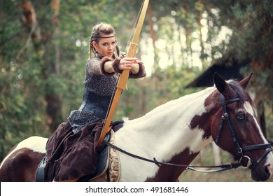 Beautiful amazon warrior riding a horse with bow and arrow in the woods