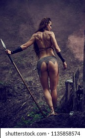 Beautiful Amazonian girl in chain mail with a spear in the woods