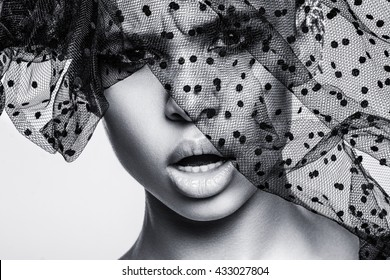 Beautiful american african girl posing. Woman with brown hair, black hat, dark skin. Attractive, sexy fashion model. Fashion shot in studio, on white background. Posing, make up, beauty, grid, veil.