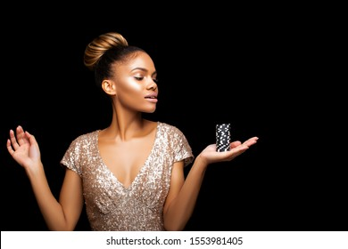 Beautiful American Girl with hairstyle bunch and Luxurious make-up is posing with a bunch of Casino Chips in her hands. Casino, Poker and Roulette. Gambling dark-skinned Woman Lucky