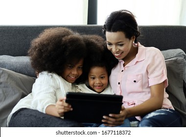 Beautiful american kid girl and mom smile portrait looking smart phone for learning at home.