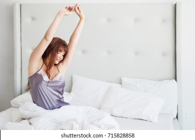 A beautiful American woman sits in bed in a gray silk nightgown and is sweetly sipped. White interior, good morning