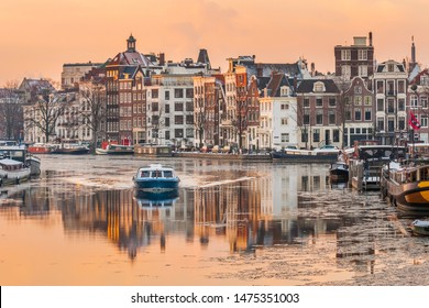 Beautiful Amsterdam, Netherlands. Canal cruise on a cold winter day on canal with ice.