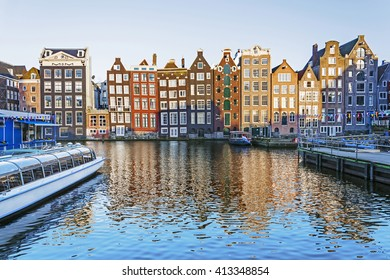 Beautiful Amsterdam scene with traditional dutch old buildings and houseboats in the canal, the Netherlands