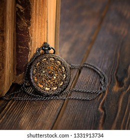 beautiful amulet and old books. inspiring picture with books. retro watches and vintage books. close up. vintage retro style, toning. soft selective focus
