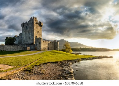 Beautiful ancient castle at a lake shore during magical sunset. Amazing and very well known location in Ireland. Landmark visited by many tourists. Peaceful, quiet, free. Setting sun and shadows.