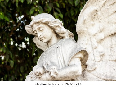 Beautiful ancient female angel  sculpture with a diffused green vegetation background