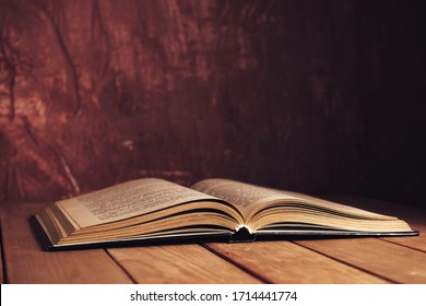Beautiful ancient open old book on a red  wooden table and dark-red wall background behind.