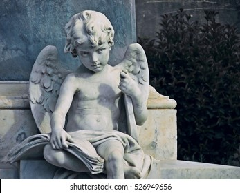 Beautiful angel child statue holding a lyre under his arm and a book on his knees. From Baroque town of Noto, Sicily.